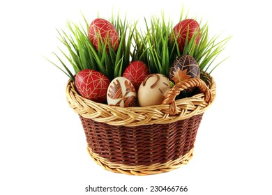 Hand-painted easter eggs in the wicker basket, white pattern, green grass