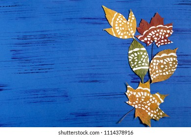 Hand-painted on dry autumn leaves by dint of paper lace napkin. Children's art project. DIY concept. Step by step photo instructions. Step 4. Finished painted leaves on blue background with copy space