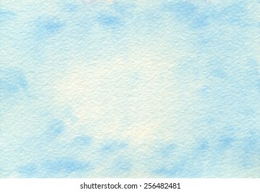 Hand-painted watercolor abstract baby blue background on rough-textured watercolor paper.