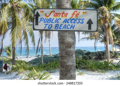 Hand-painted wooden sign on coconut palm directs visitors to beautiful public beach in Tulum on the the Mexican Riviera