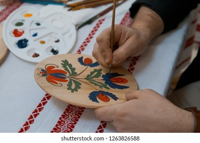 handpainting on handmade decorative wooden round plate, man's hand paints a bright floral pattern with a brush, Petrykivka painting style
