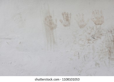 handprints and dirty stained on white concrete wall in nature light