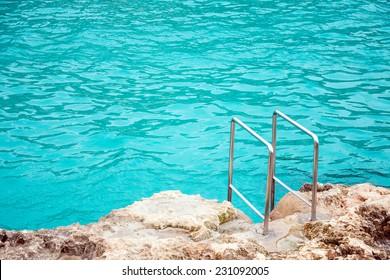Handrails mounted on rock near the sea.