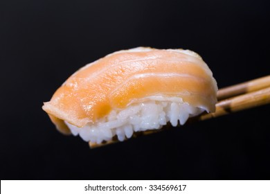 Hand-rolled sushi close-up black background Salmon