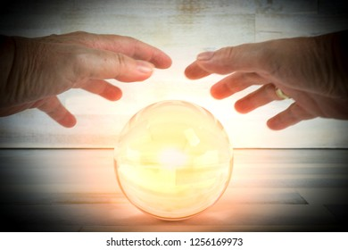 Hands above a glowing crystal ball