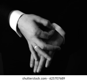 Hands adjust the sleeve of a business suit shirt