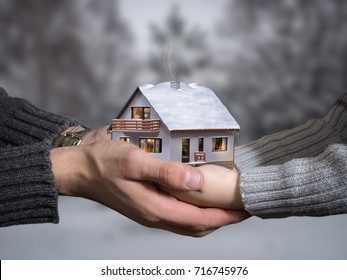 The hands of an adult and child hold a beautiful house. The concept of private housing, buy a country house
