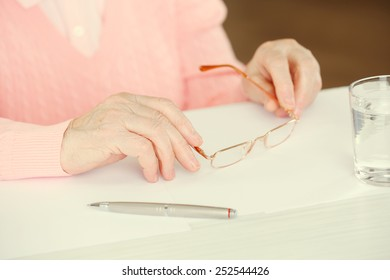 Hands of adult woman with pen, glasses and glass of water on table