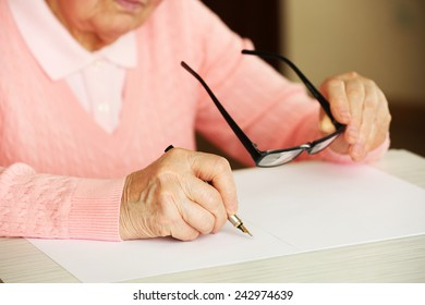 Hands of adult woman writing with pen and glasses, on table, on light background