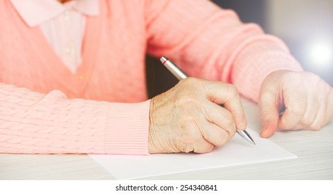 Hands of adult woman writing with pen on table, close-up