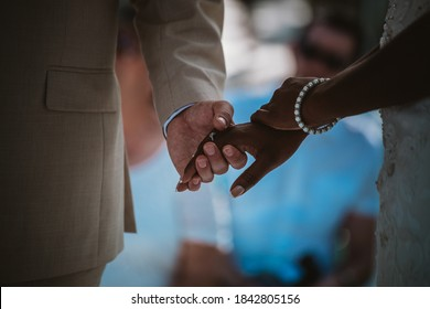 Hands of African - American and Caucasian newlyweds. Interracial wedding. Bride and groom holding hands