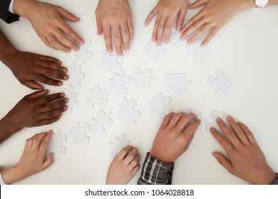 Hands of african and caucasian people help in assembling puzzle together, multiracial team engaging in finding best business solution for successful teamwork, teambuilding concept, top close up view