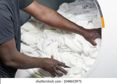 The hands of an african male laundry worker in the inn give a clean towel from the washing machine. Washing machine in stylish hotel laundry. Laundry in the hotel.