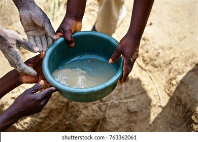 The hands of African men are shown passing a bucket of dirty water.