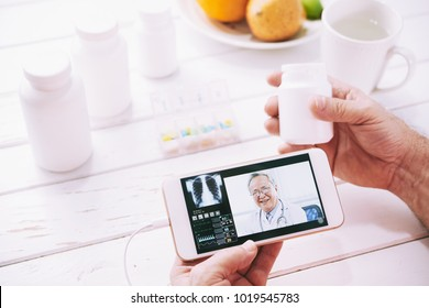 Hands of aged patient consulting general practitioner online on his smartphone