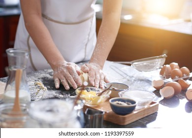 Hands of anonymous woman covered with flour kneading cookie dough on messy kitchen table, sunshine illuminating room