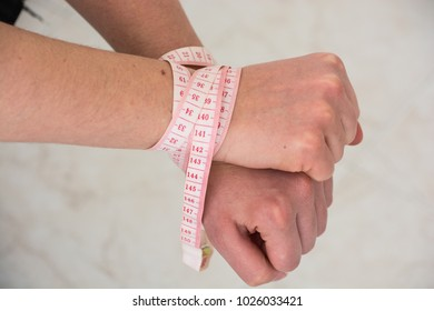 hands of an anorexic girl tied with meter