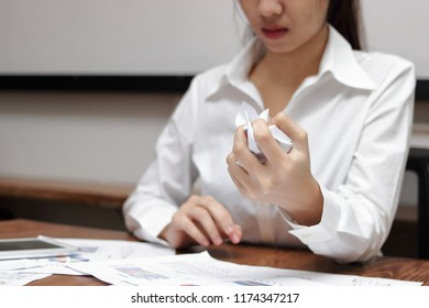 Hands of anxiety businesswoman holding crumpled paper on workplace in office. Failure and tired business concept.