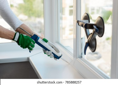 Hands applying silicone sealant that defending from water leaks and mildew. Home repair and maintenance services.