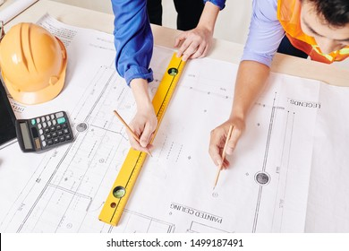 Hands of architect and civil engineer working on construction plan of building, view from above