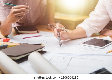 Hands of architect or engineer using drawing compass with blueprint on desk in office.Team of architects engineer discussing and check documents and business workflow.Construction concept.