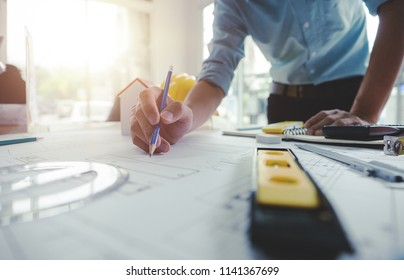 Hands of architect or engineer using pencil working with blueprint on desk in office . Engineering tools and construction concept. Architect and Business concept.Selective focus,Vintage effect.