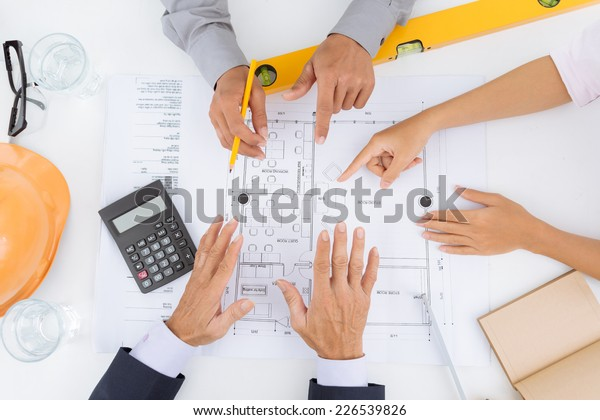 Hands of architects planning a house project, view from the top