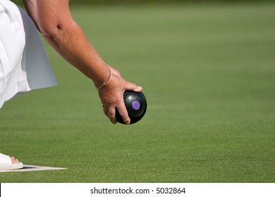 Hands and arm of a female holding a lawn bowling ball about to bowl.