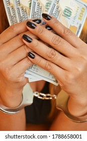 Hands of an arrested lady with money and handcuffs