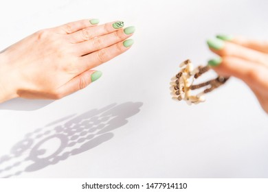 Woman's hands with art leaf nails design and green manicure holding wooden handmade necklace.
