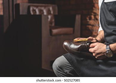 hands of artisan holding shoe and cleaning it