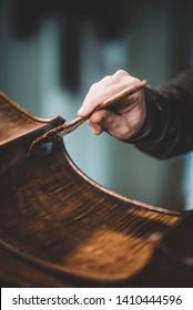 hands of artisan luthier varnishing, building a double bass