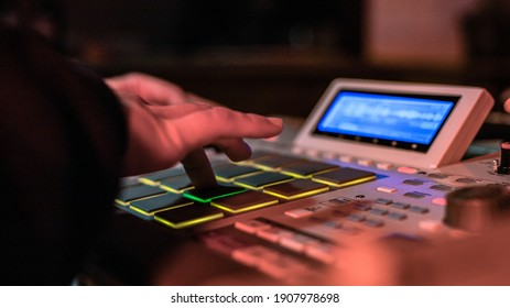 The hands of an artist creating music with his drum machines under red light.