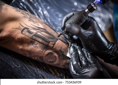 Hands of the artist tattooing of man's skin