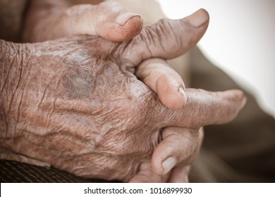 Hands Asian elderly woman grasps her hand on lap, pair of elderly wrinkled hands in prayer and Traces of hard work, World Kindness older and Adult care,  Mother day people concept