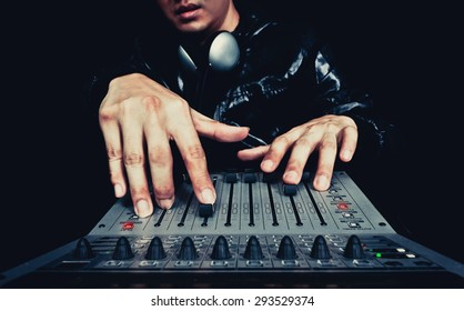hands of asian handsome DJ, producer working on digital studio mixer for night club, radio, TV broadcasting background