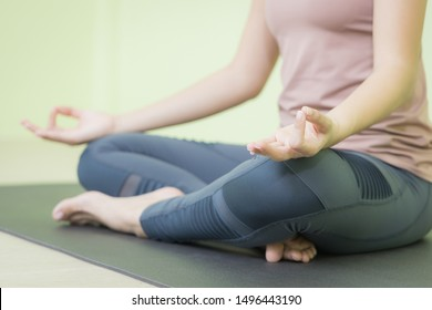 Hands of Asian lady meditation yoga in peaceful studio, close up shot