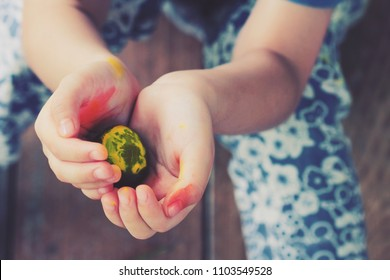 Hands of Asian little girl holding pebble rock that painted yellow color on it.Girl's hand were  painted in colorful paints.Concept of d.i.y arts or handmade  things from kids.