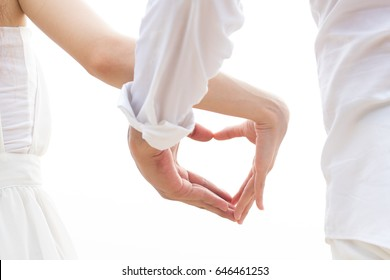 The hands of Asian lovers holding hearts together on a white background.