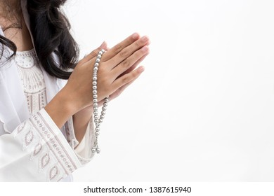 Hands of Asian muslim woman wearing prayer beads welcoming guests / Ied Fitr Greeting in white background