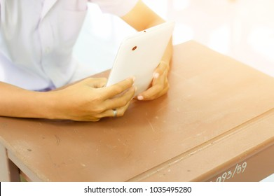 Hands of Asian schoolboy holding the white tablet to searching knowledge by using wifi internet connection,on brown wood student desk in classroom when leisure time.Concept is Borderless Education.