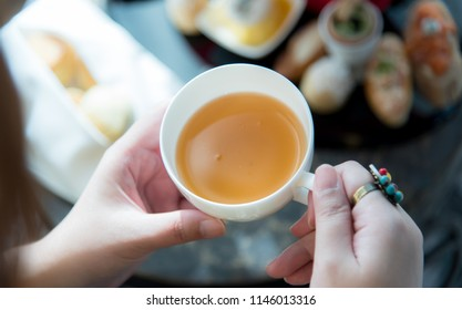 Hands of Asian woman hold a white porcelain cup of fresh brew tea during afternoon tea or high tea with variety of freshly baked scones, sweets and desserts background. Natural lighting.