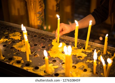 The hands of Asian women are burning candles in the temple for religious ceremonies and requesting blessings. A large number of yellow candles shine beautifully together with tears on the metal floor.