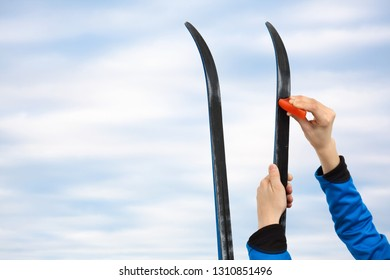 hands athlete preparing skis for the race, against the sky