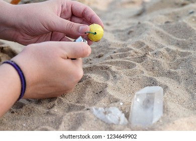 Hands attempting to light a small smoke bomb in the sand