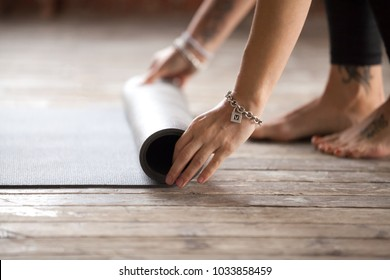 Hands of an attractive young woman folding black yoga or fitness mat after working out at home in living room or in yoga studio. Healthy lifestyle, keep fit, weight loss concepts. Close up view photo