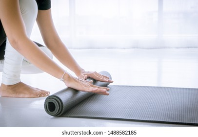 Hands of an attractive young woman folding gray yoga or fitness mat after working out at home in a living room or in a yoga studio. Healthy lifestyle, keep fit and firm concepts. Close up view photo