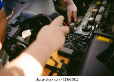 hands of an auto mechanic close-up. servicing and caring for a car engine