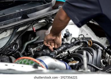 Hands of auto mechanic repairing car engine in garage. Maintenance car. - Shutterstock ID 1927356221