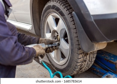 hands of automotive mechanic unscrewing nuts with pneumatic impact wrench during car wheels season changing